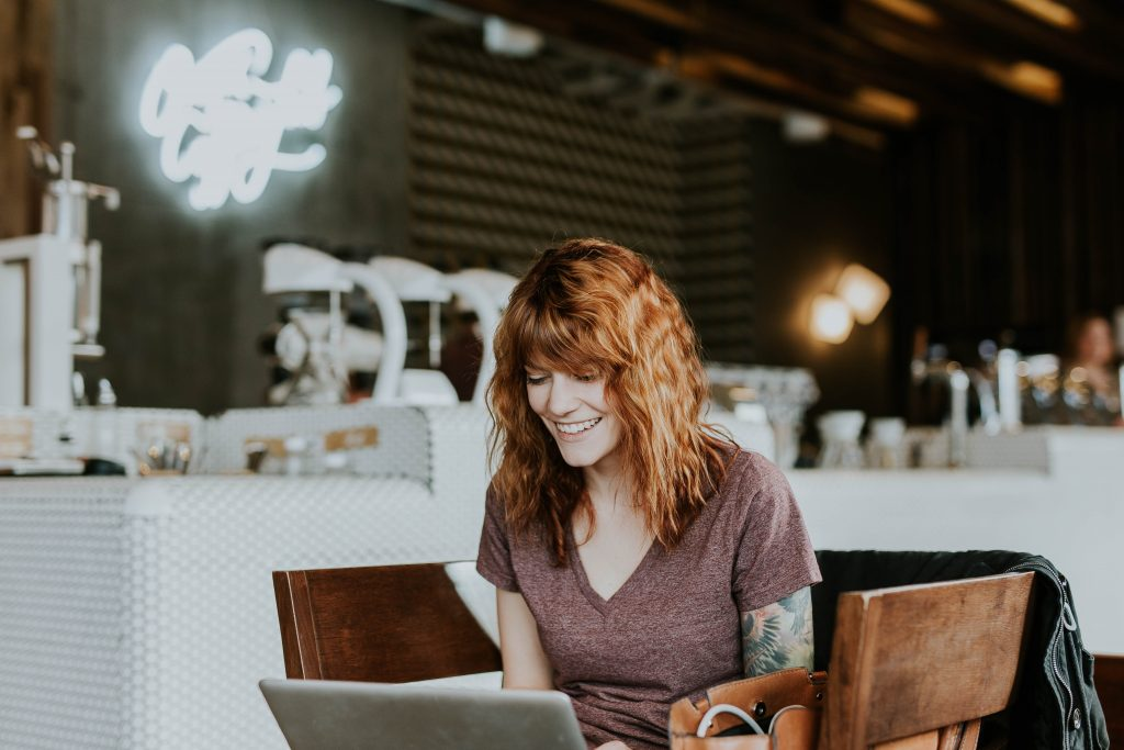 Woman smiling at her laptop because of her online classes