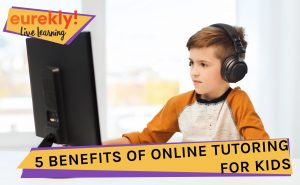 A boy wearing headphones sitting in front of the computer