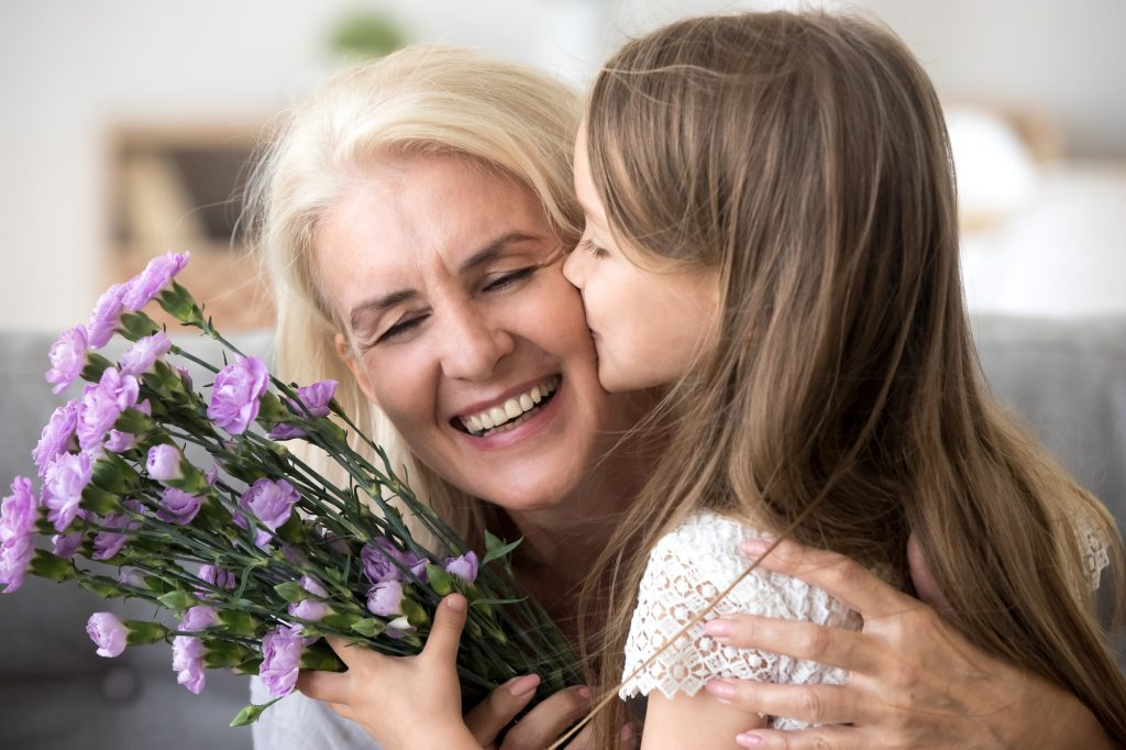 A girl kissing her granny and giving her a bunch of flowers
