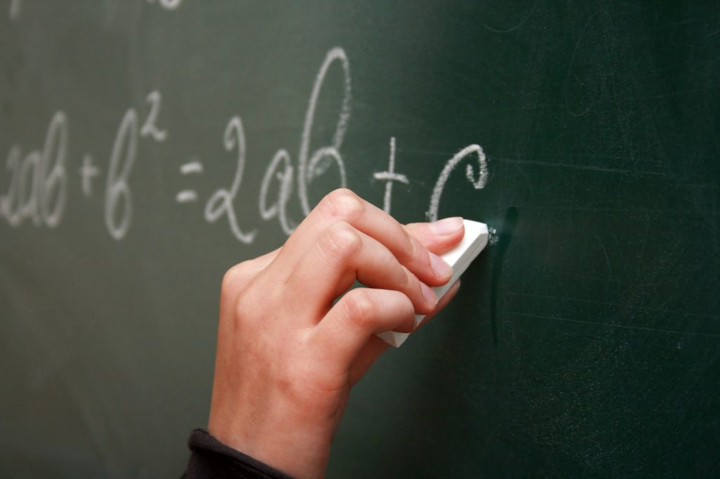 A teacher's hand writing on the chalkboard