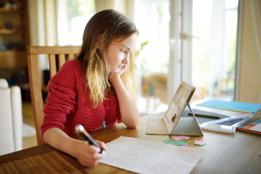 A schoolgirl doing her homework with a digital tablet at home
