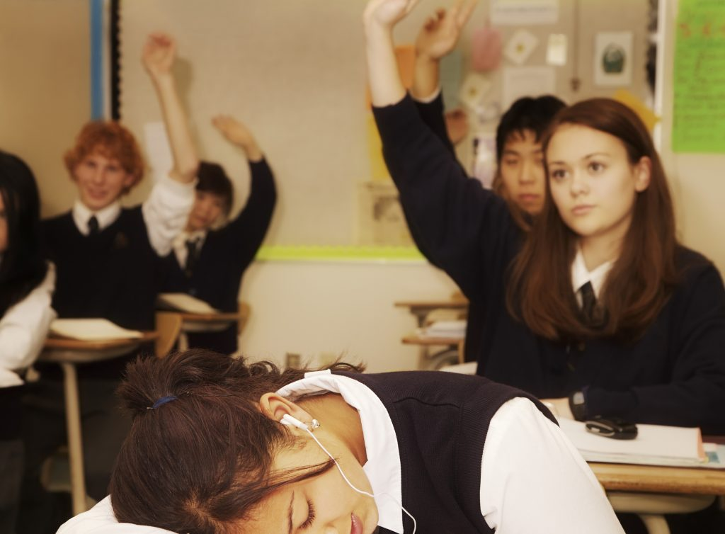 A school girl sleeping during the class while other pupils are working with the teacher