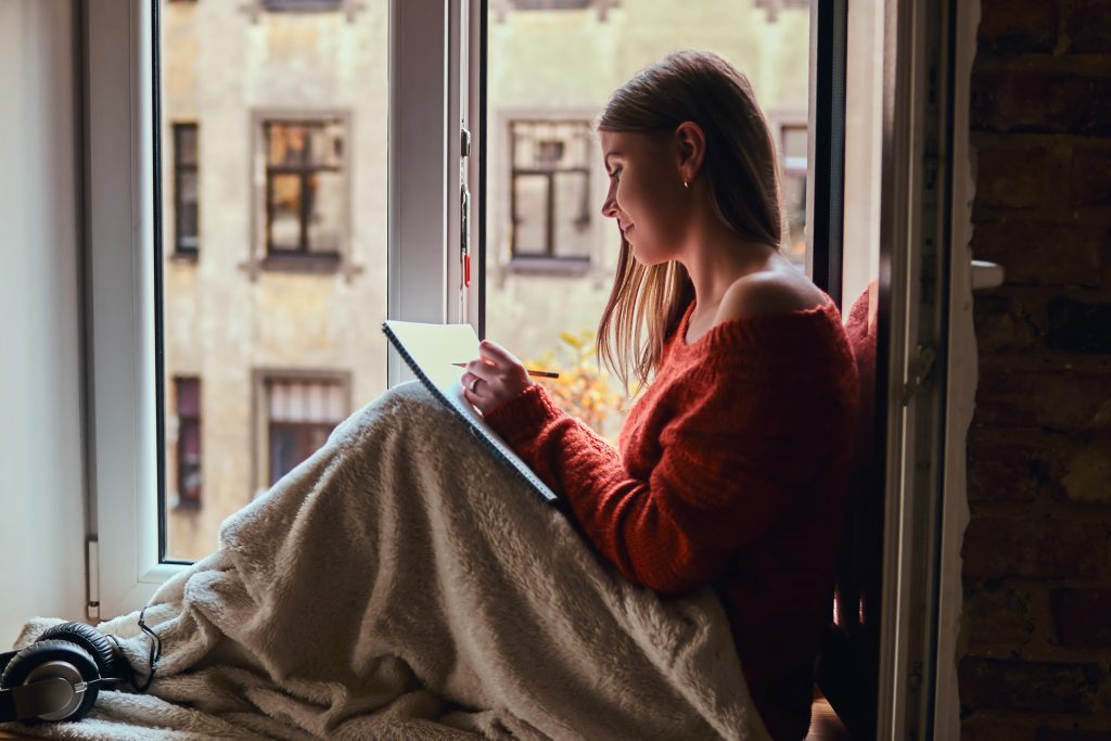 Girl in a warm sweater making notes in her notebook sitting on the window