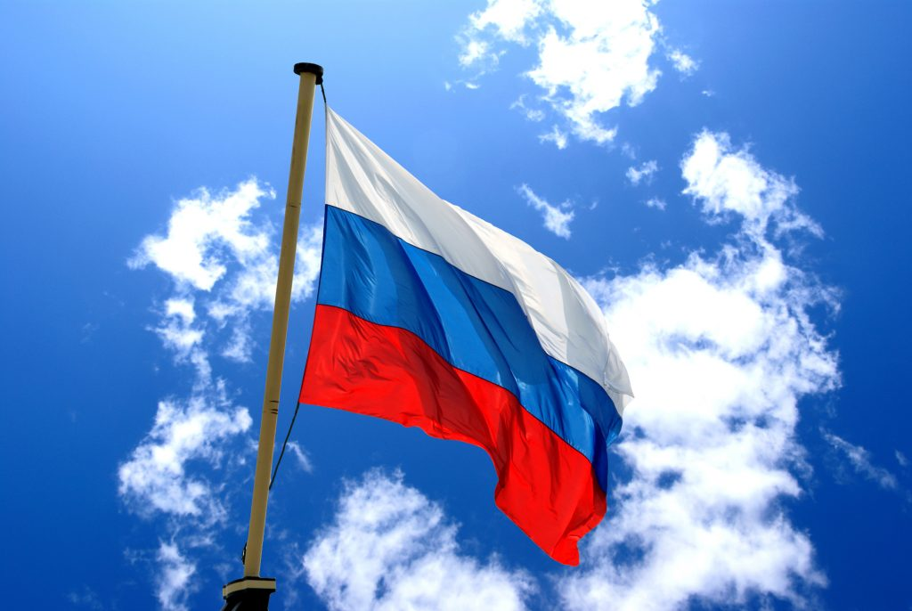 Russian national flag on the blue sky with clouds