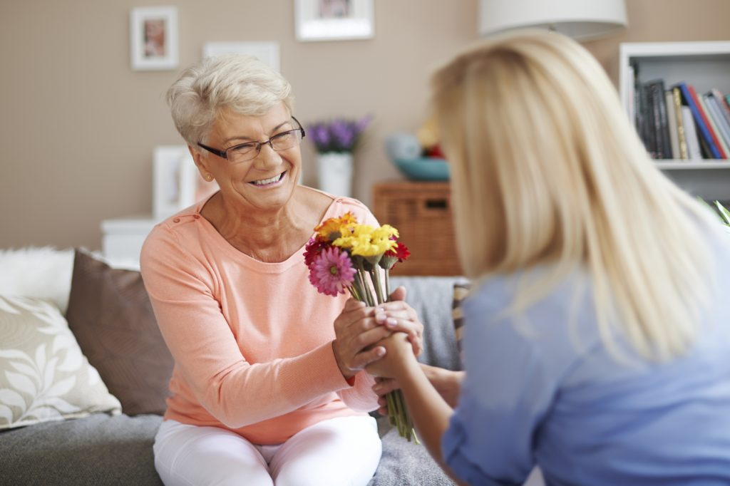 Young girl giving flowers to a smiling elderly woman
