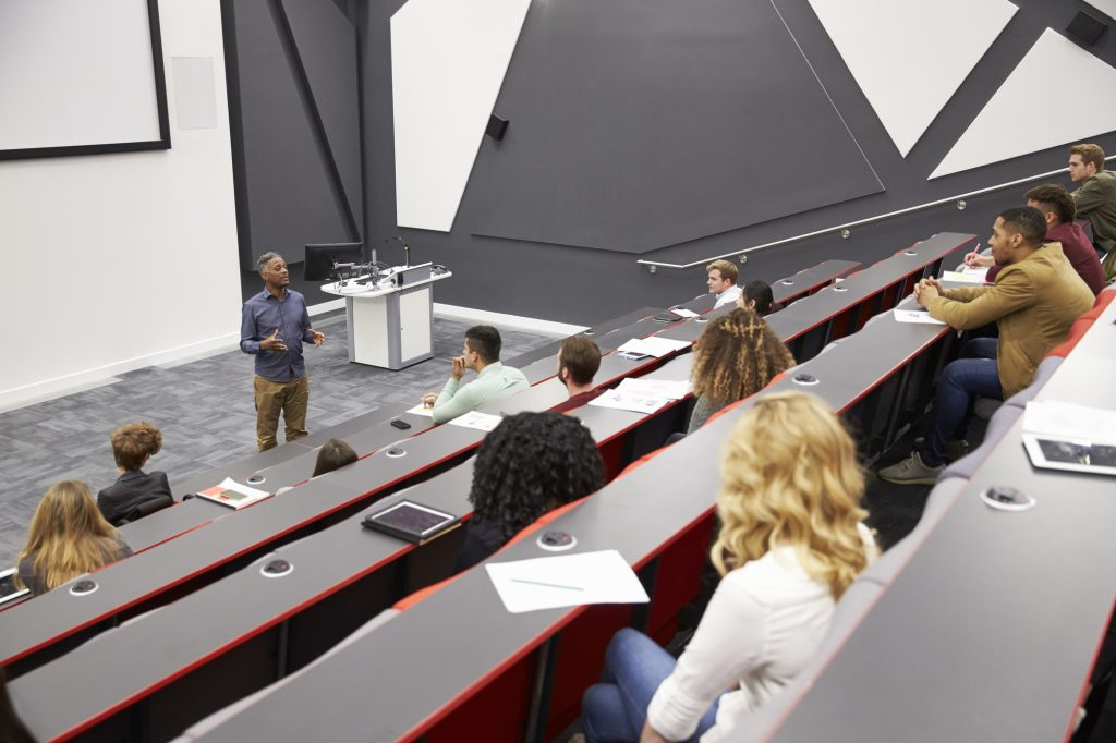 Male teacher lecturing students in a large audience