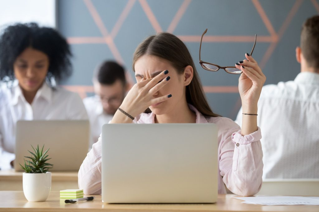 Young woman taking off her glasses and rubbing her eyes tired of computer work