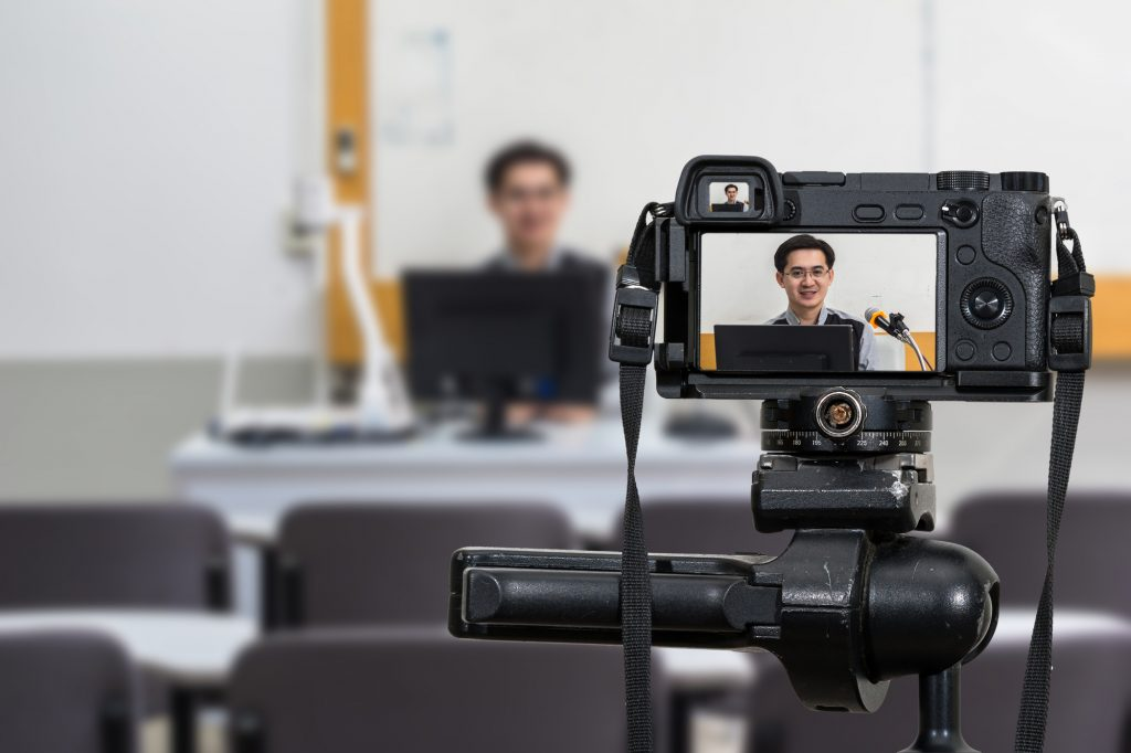 Professional digital camera recording video of an Asian teacher in the classroom