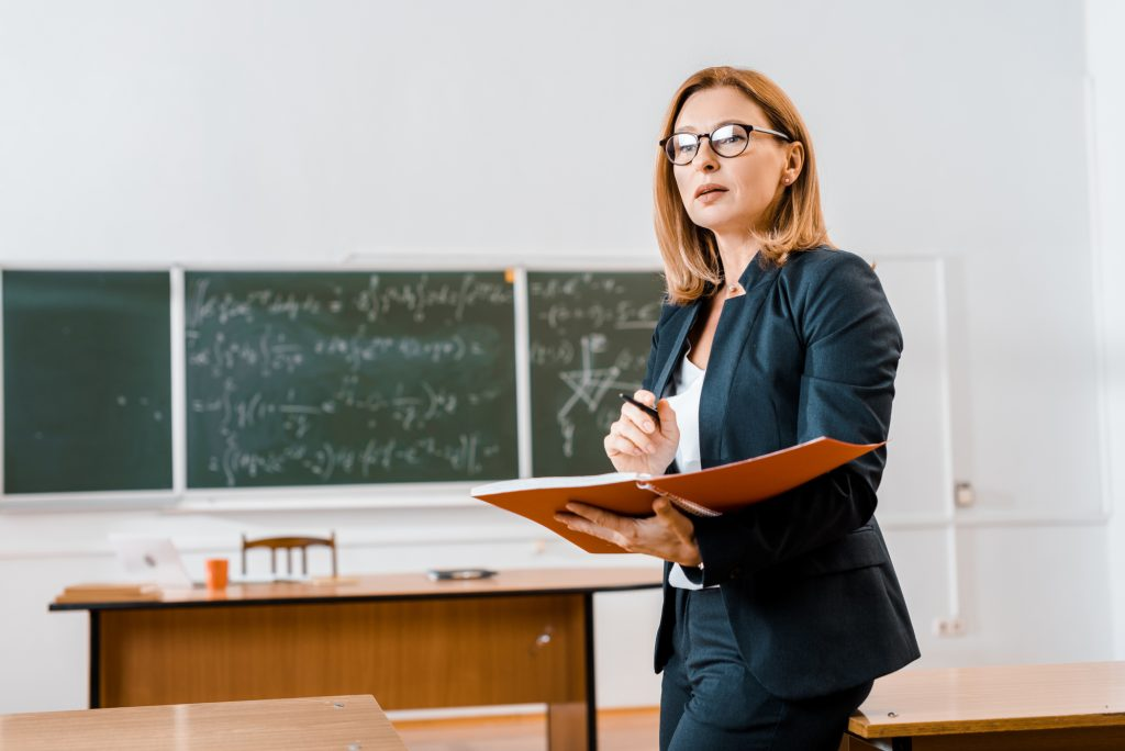 Teacher wearing glasses and holding a folder