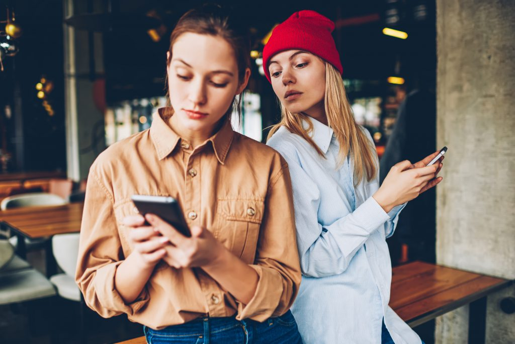 Two girls in casual outfit ignoring live communication while spending their time browsing social networks in modern smartphones