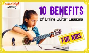 Little girl playing the guitar in front of her laptop
