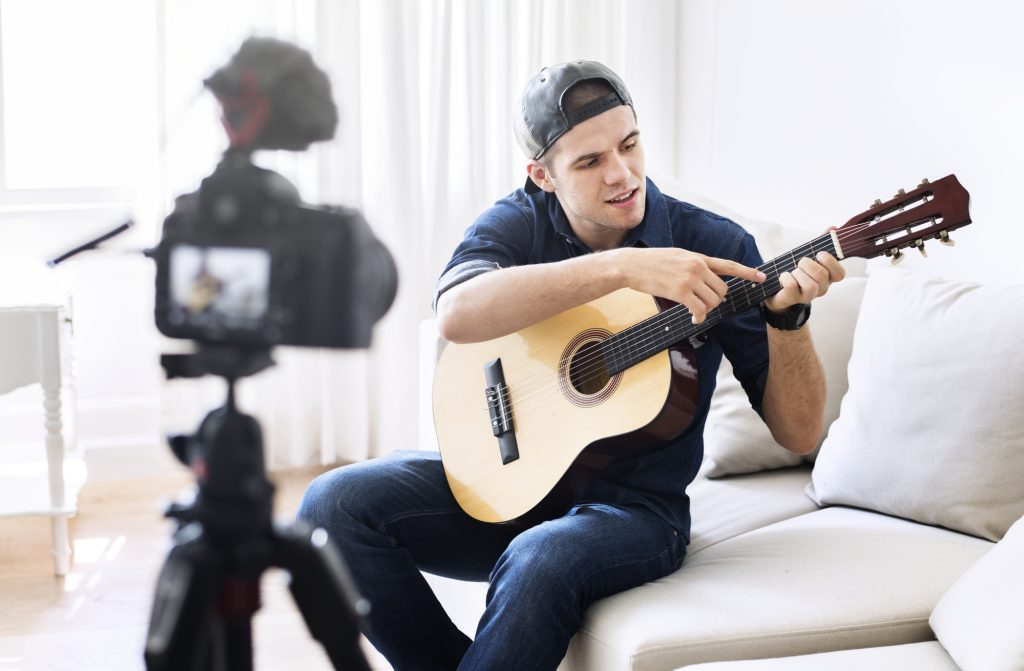 Young man sitting in front of a digital camera and holding a guitar