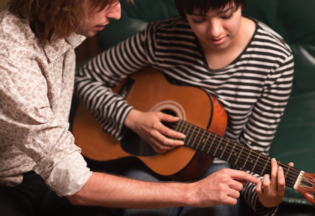 Young male guitar tutor teaching a girl to play the guitar