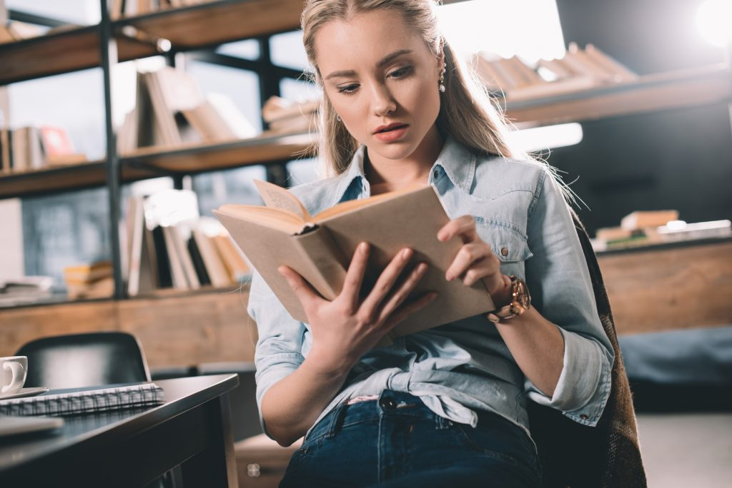Girl reading a book in a library