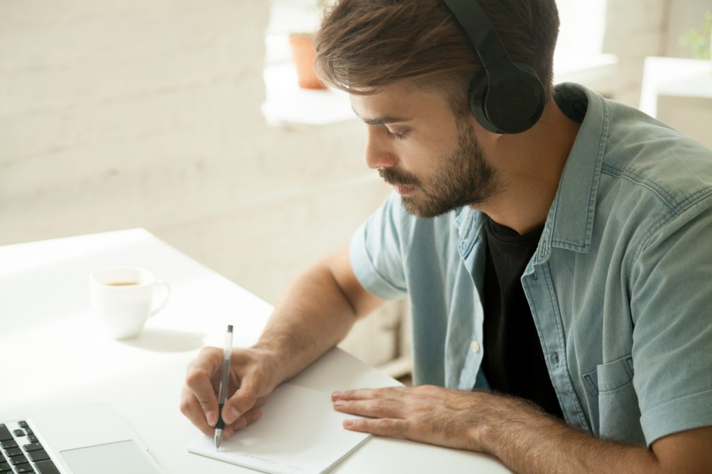 Young man wearing headphones sitting in front of his laptop and writing something on a piece of paper